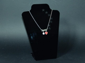 Black plexiglass necklace display with stars carved on it